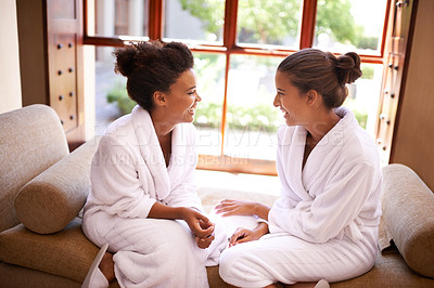 Buy stock photo Shot of two friends in bathrobes talking an laughing at a spa