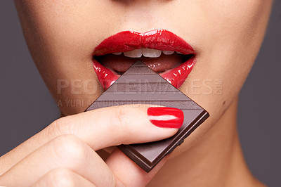 Buy stock photo Closeup portrait of a cute young female biting on a chocolate bar
