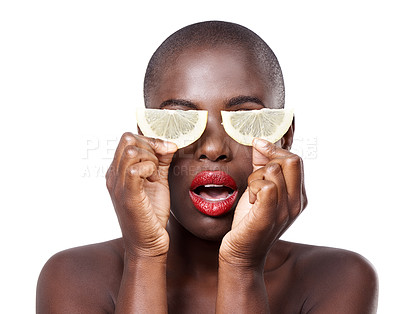 Buy stock photo Studio shot of a beautiful model holding lemon slices up to her eyes