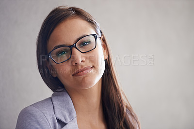 Buy stock photo Portrait of a successful young businesswoman standing against a gray wall