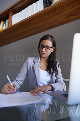Buy stock photo Shot of an attractive young businesswoman working on some paperwork at her desk