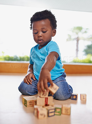 Buy stock photo Full length shot of a baby boy playing with building blocks at home