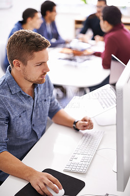 Buy stock photo Shot of a young designer working at his computer with colleagues in the background