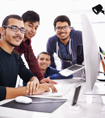 Buy stock photo Cropped shot of young students gathered around a computer