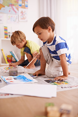 Buy stock photo Shot of two young boys painting pictures at home