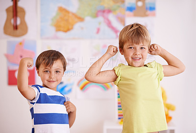 Buy stock photo Two young boys flexing their muscles while standing in their bedroom