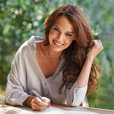 Buy stock photo Portrait of an attractive young woman writing in a relaxed environment outdoors