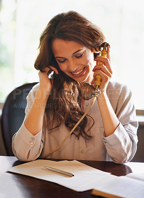 Buy stock photo Shot of an attractive woman speaking on a vintage telephone at home