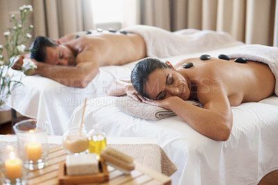 Buy stock photo Shot of a mature couple enjoying a hot stone treatment