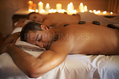 Buy stock photo Shot of a mature couple enjoying some hot stone therapy