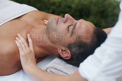 Buy stock photo Cropped shot of a handsome man enjoying a massage at a health spa