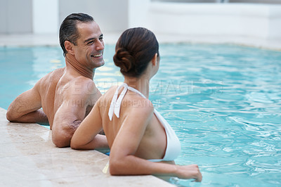 Buy stock photo Cropped shot of a couple relaxing in a pool