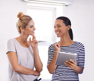 Buy stock photo Shot of two young woman working on a digital tablet