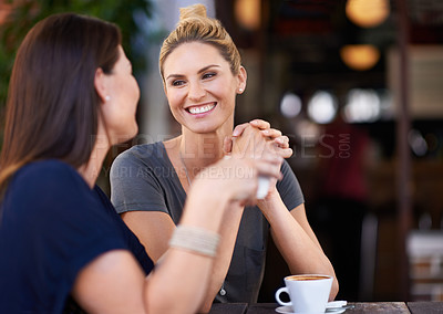 Buy stock photo Two attractive women sitting outside a cafe