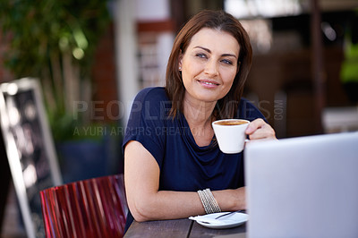 Buy stock photo Shot of an attractive woman using her laptop at a coffee shop