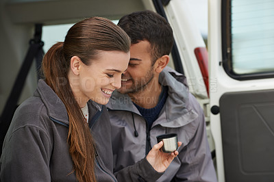 Buy stock photo Cropped shot of a young couple sitting at the back of their car while on a roadtrip