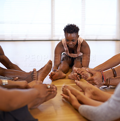 Buy stock photo Shot of a young woman stretching with her fellow dancers