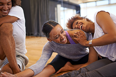 Buy stock photo Shot of three happy young women dancers stretching on the floor