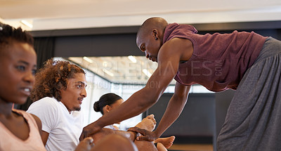 Buy stock photo Shot of a dance instructor helping his students stretch in a studio