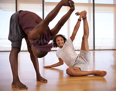 Buy stock photo Shot of two male dancers stretching in the dance studio