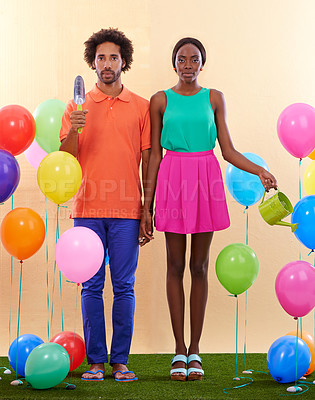 Buy stock photo An awkward african couple surround by colorful balloons while holding hands
