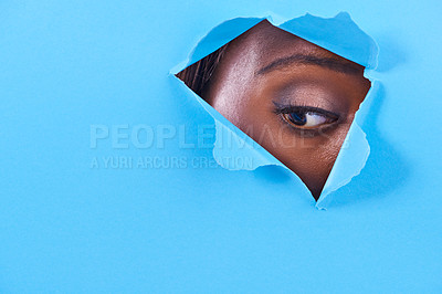 Buy stock photo A view of a woman's eye looking through a hole in some colorful paper