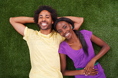 Buy stock photo A young african couple lying on the grass together