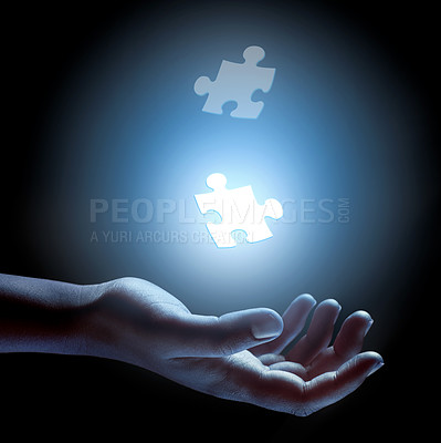 Buy stock photo Conceptual shot of jigsaw pieces floating over a person's hand building a puzzle