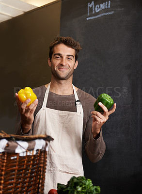 Buy stock photo A young man holding a yellow and green pepper in a kitchen