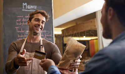 Buy stock photo Shot of a handsome young man making a sale at his food stall