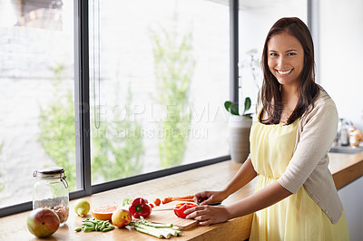 Buy stock photo A young woman preparing food in her kitchen