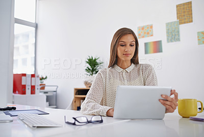 Buy stock photo Shot of a young woman using her digital tablet in the office