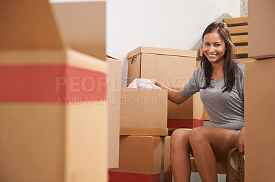 Buy stock photo Portrait of a beautiful young woman surrounded by boxes in her new home