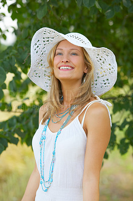 Buy stock photo Fresh-faced portrait of a pretty woman with a summer hat standing outdoors