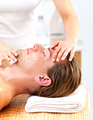 Buy stock photo Young happy man receiving facial massage by female masseuse. Enjoying a healthy holiday at the day spa.