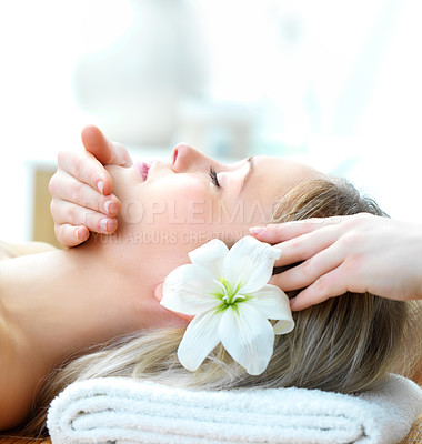 Buy stock photo Profile of a beautiful woman with a flower in her hair lying down receiving a relaxing head massage - copyspace