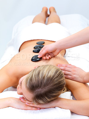 Buy stock photo Hot stone massaging with hands - Portrait of a beautiful young girl at the day spa with black stones on her bare back
