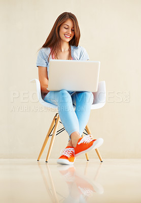Buy stock photo Full length of pretty young girl sitting on chair using laptop and smiling