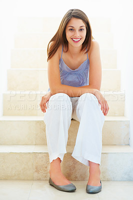 Buy stock photo Full length of pretty young woman sitting on stairs and smiling