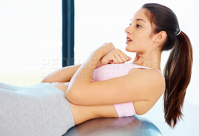 Buy stock photo Young woman doing sit ups on pilates ball