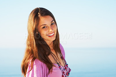 Buy stock photo Portrait of beautiful young woman standing against sky and smiling