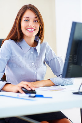 Buy stock photo Portrait of businesswoman sitting at an office table and using computer