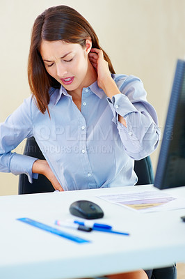 Buy stock photo Young businesswoman in pain holding her neck and lower back
