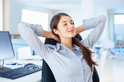 Buy stock photo Young female executive relaxing in an office chair with hands behind head