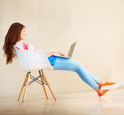 Buy stock photo Full length of smiling young girl sitting on chair using laptop