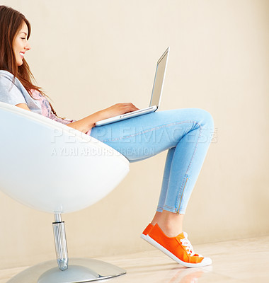Buy stock photo Pretty young girl sitting in chair while using a laptop and smiling