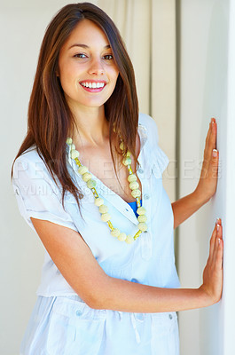 Buy stock photo Portrait of an attractive young woman standing with hands on wall and smiling