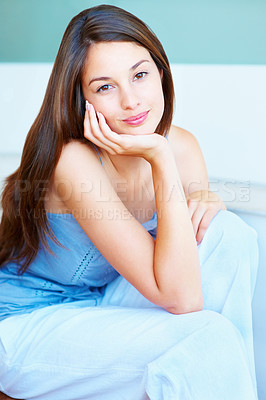 Buy stock photo Portrait of an attractive young girl sitting with hand on face and smiling