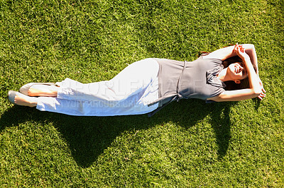 Buy stock photo Top view of young woman lying in the grass and enjoying the sunny weather