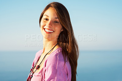 Buy stock photo Portrait of an attractive young female standing against sky and smiling